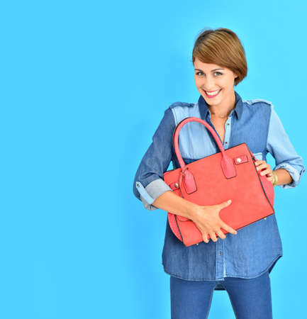 25 years old: Attractive young woman on blue background holding red purse