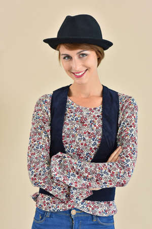 25 years old: Cheerful trendy girl with hat standing on beige background