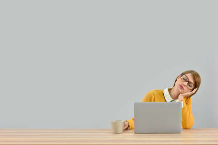 Working girl in front of laptop being tired, isolated Stock Photo