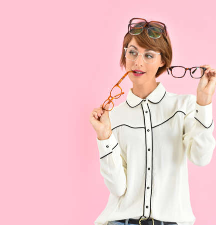 Cheerful trendy girl having trouble choosing eyeglasses Standard-Bild