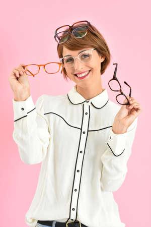 Alegre chica de moda que tiene problemas para elegir anteojos Foto de archivo