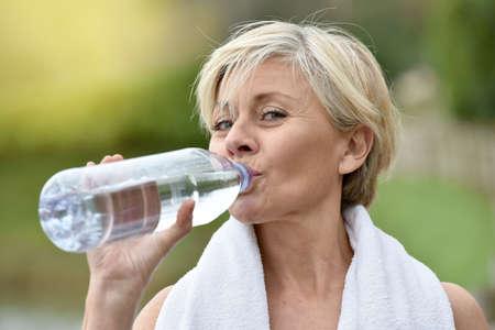 hacer footing: Mujer mayor que el agua potable después del ejercicio Foto de archivo