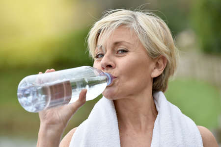 one senior: Senior woman drinking water after exercising