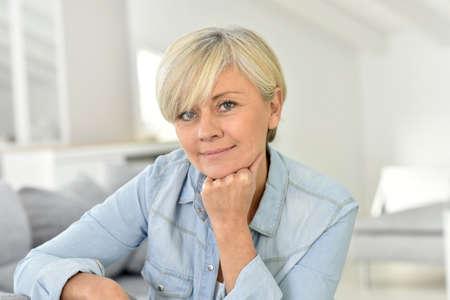 mature women: Portrait of senior woman sitting on sofa
