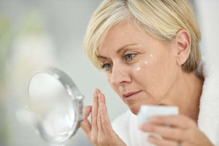 aging: Senior woman in bathroom applying anti-aging lotion