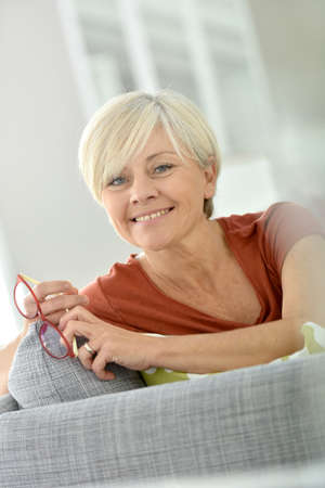 woman smiling: Cheerful senior woman sitting on couch at home Stock Photo