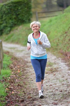 senior woman: Senior woman jogging outside with earphones on Stock Photo