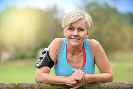 old fence: Portrait of smiling senior woman relaxing after exercising