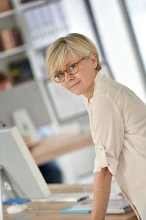 businesswoman standing: Senior businesswoman standing in office Stock Photo