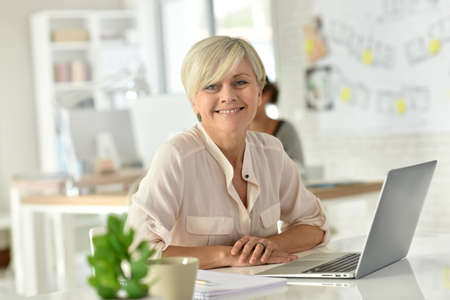 beautiful mature woman: Senior businesswoman in office working on laptop computer