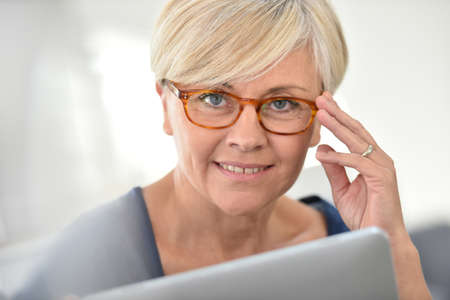 browsing: Senior woman with eyeglasses browsing on digital tablet