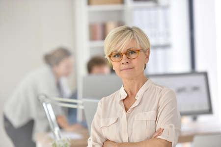 workteam: Senior businesswoman standing in office Stock Photo