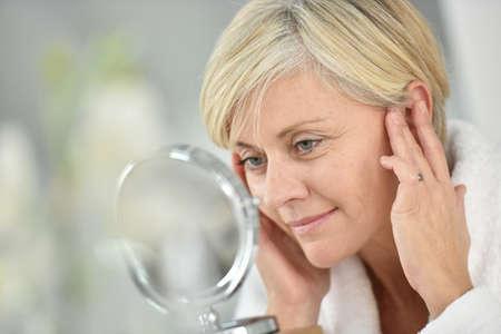 Hogere vrouw in de badkamer toepassing van anti-aging lotion Stockfoto