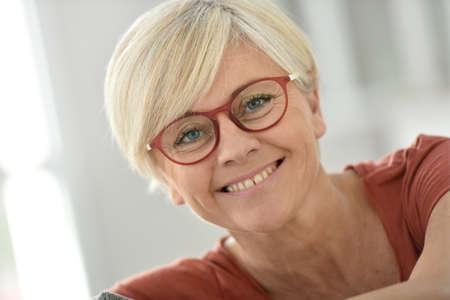 Portret van lachende senior vrouw met bril Stockfoto