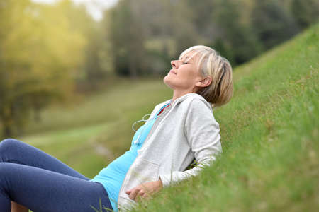 meditation woman: Senior woman in fitness outfit relaxing in park Stock Photo