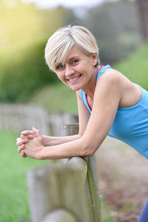 mujeres ancianas: Retrato de la mujer mayor atlético inclina en la cerca