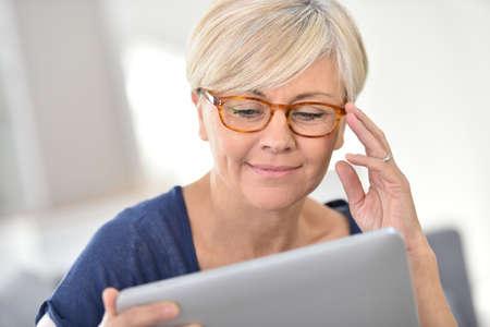 Hogere vrouw met bril bekijkt digitale tablet