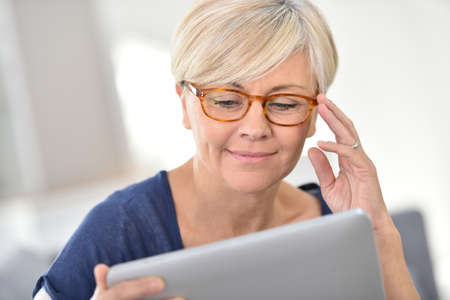 attractive couch: Senior woman with eyeglasses browsing on digital tablet