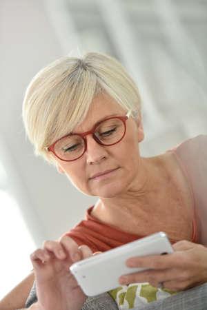 websurfing: Senior woman with eyeglasses websurfing on smartphone Stock Photo