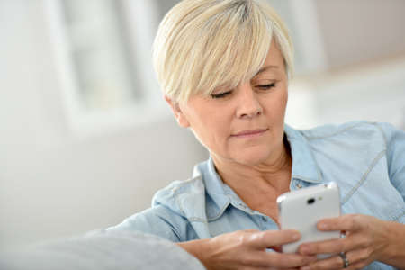 woman on phone: Senior woman sending message with smartphone