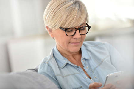 mujeres maduras: Senior woman with eyeglasses sending text message