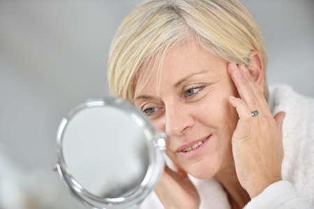 Superior de la mujer en el baño aplicar anti-envejecimiento loción