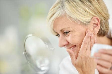 Senior woman in bathroom applying anti-aging lotion Reklamní fotografie - 48552587