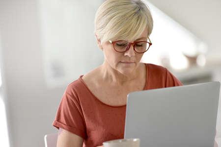 femme blonde: Senior femme � la maison en utilisant un ordinateur portable
