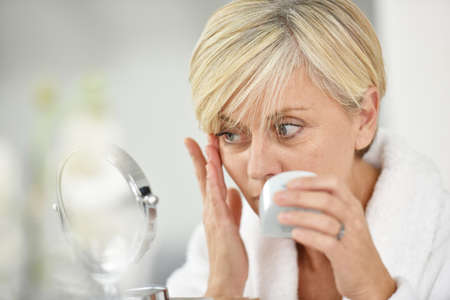 antiaging: Senior woman in bathroom applying anti-aging lotion