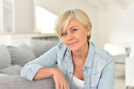 blonde yeux bleus: Portrait de femme senior assis sur le sofa