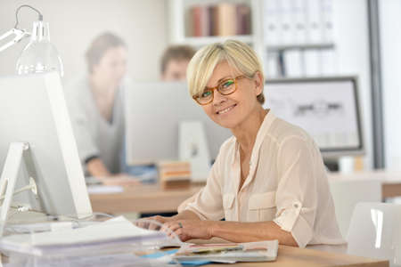 Lachende senior zakenvrouw werken in kantoor Stockfoto