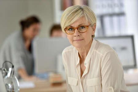 femme blonde: Senior businesswoman debout dans le bureau Banque d'images