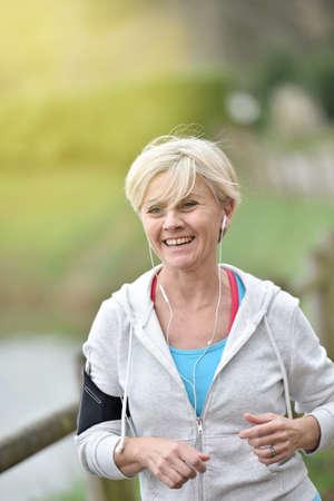 mujeres corriendo: Mujer mayor que activa al aire libre con los auriculares puestos Foto de archivo