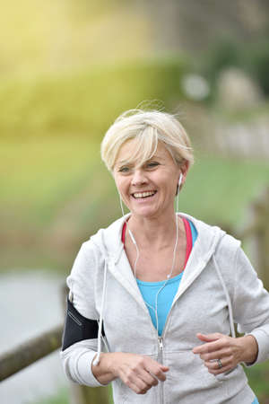senior exercise: Senior woman jogging outside with earphones on Stock Photo