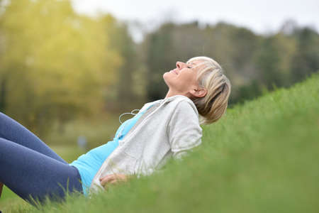 Senior woman in fitness outfit relaxing in park Stock Photo