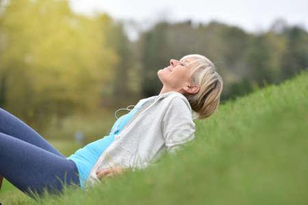 señora mayor: Superior de la mujer en traje de aptitud se relaja en parque