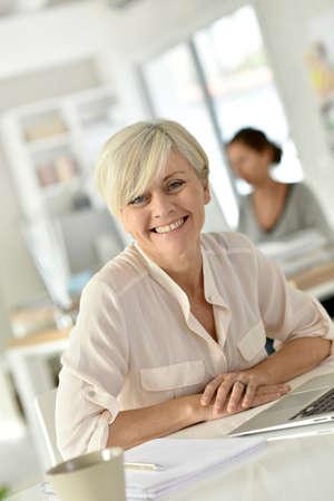 old women: Senior businesswoman in office working on laptop computer