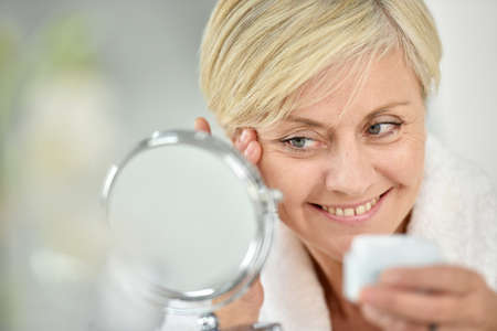 Ältere Frau im Badezimmer, das Anti-Aging-Lotion Standard-Bild