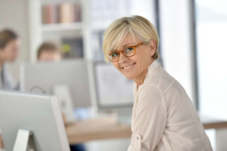 Senior zakenvrouw staande in het kantoor Stockfoto