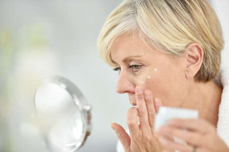 Senior woman in bathroom applying anti-aging lotion