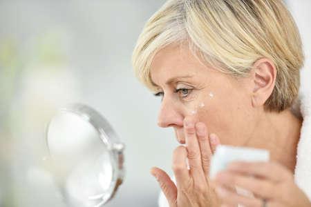 aging face: Senior woman in bathroom applying anti-aging lotion