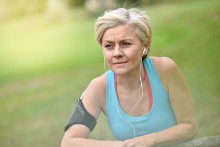 blonde woman: Portrait of smiling senior woman relaxing after exercising