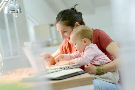 Vrouw werken van thuis uit met de baby op schoot Stockfoto