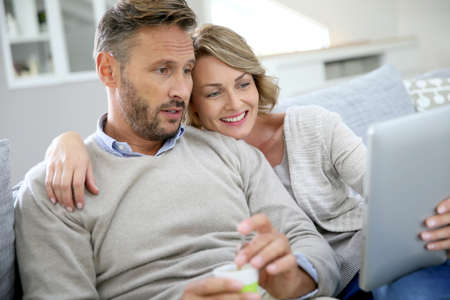 couple relaxing: Middle-aged couple relaxing in sofa and using tablet