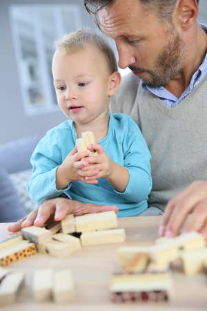 dad son: Daddy with 2-year-old boy playing with wooden blocks
