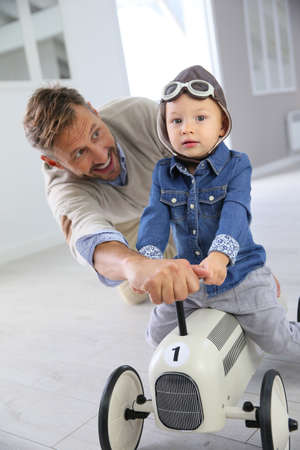 father and son: Man helping little boy on a riding toy
