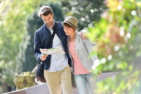 Jeune couple marchant dans le parc et la lecture de carte de la ville