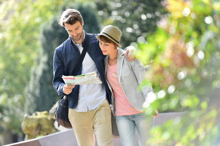 caminando: Pareja joven caminando en el parque y la lectura de un mapa de la ciudad