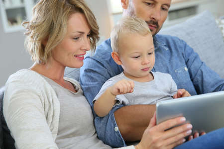woman tablet: Parents with baby boy playing with digital tablet