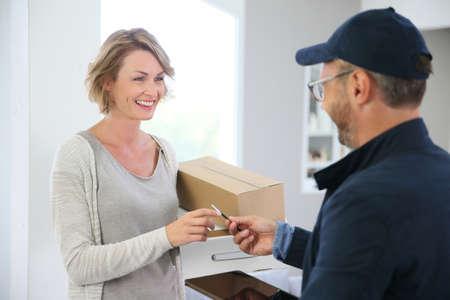 Mujer que recibe paquete de hombre de entrega